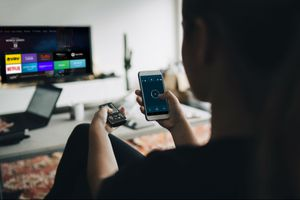 A woman using the Fire Stick TV remote app to control her Fire TV.