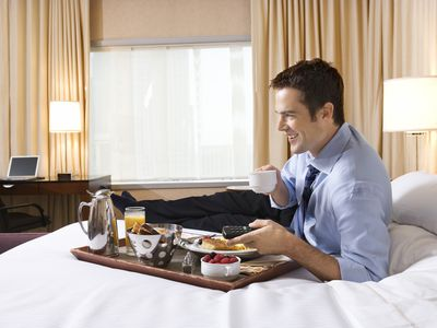 A man in a business suit lying on a hotel room bed while holding a TV remote and watching his Amazon Fire Stick on the television.