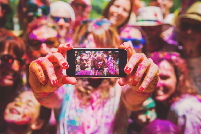 People covered in paint taking a selfie on an iPhone