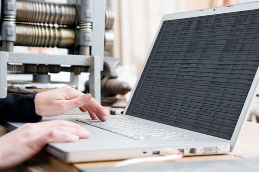 Woman creating database on laptop