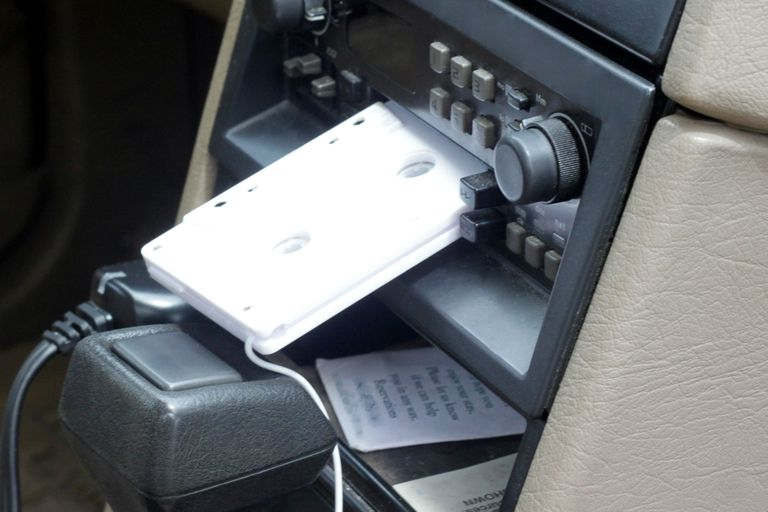 A cassette tape adapter inserted into a car radio.