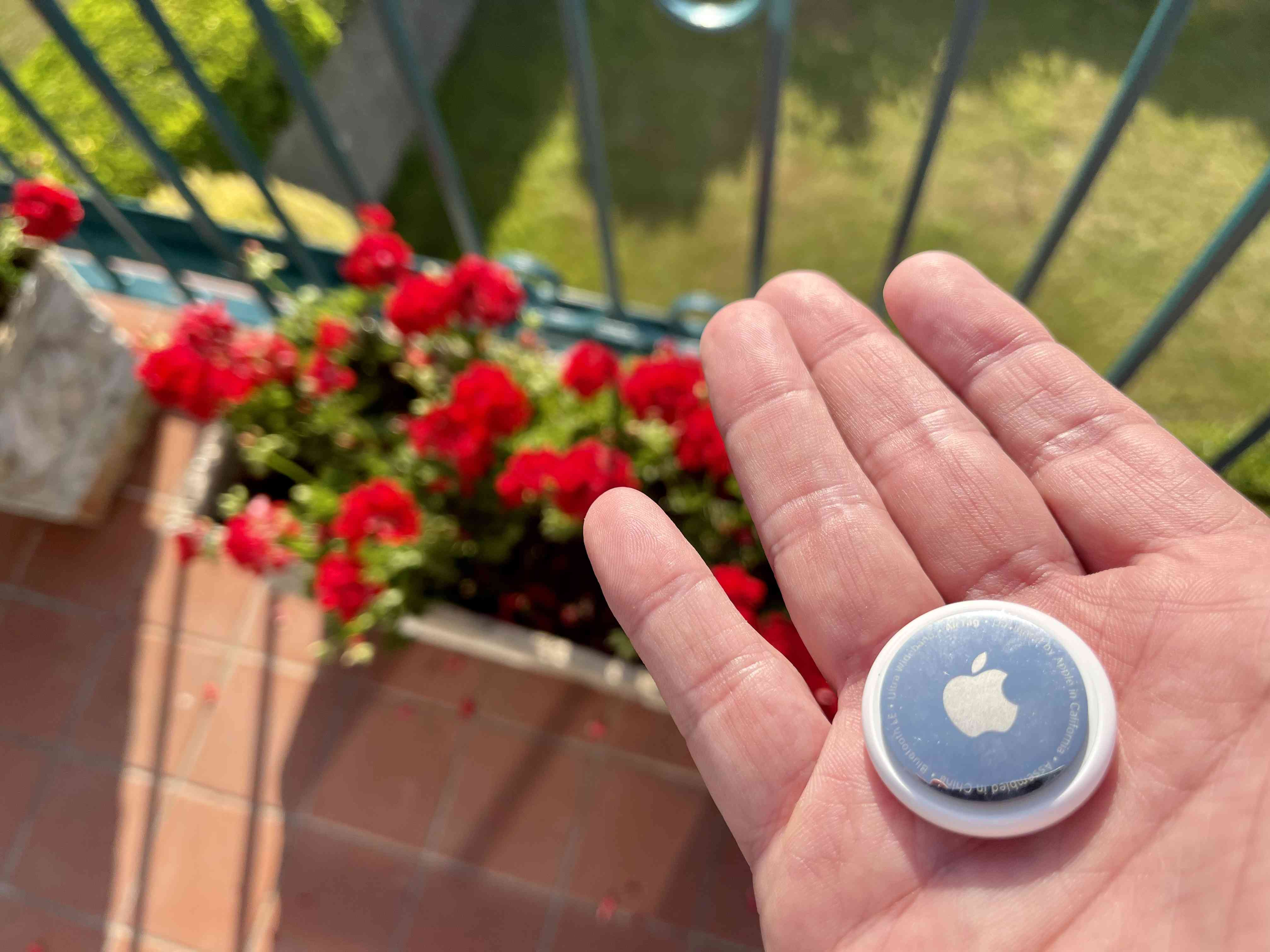 Closeup of someone holding an Apple AirTag outdoors.