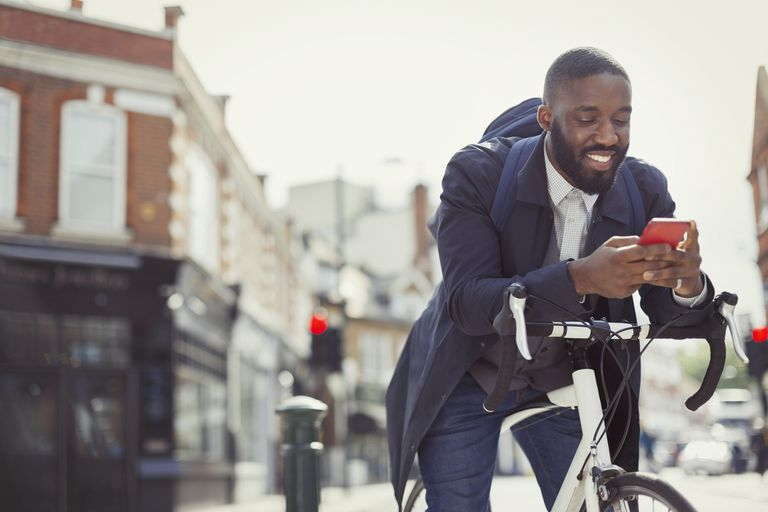 Young businessman commuting with bicycle, emailing with cell phone