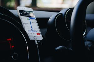 A smartphone showing Apple Maps in a car.