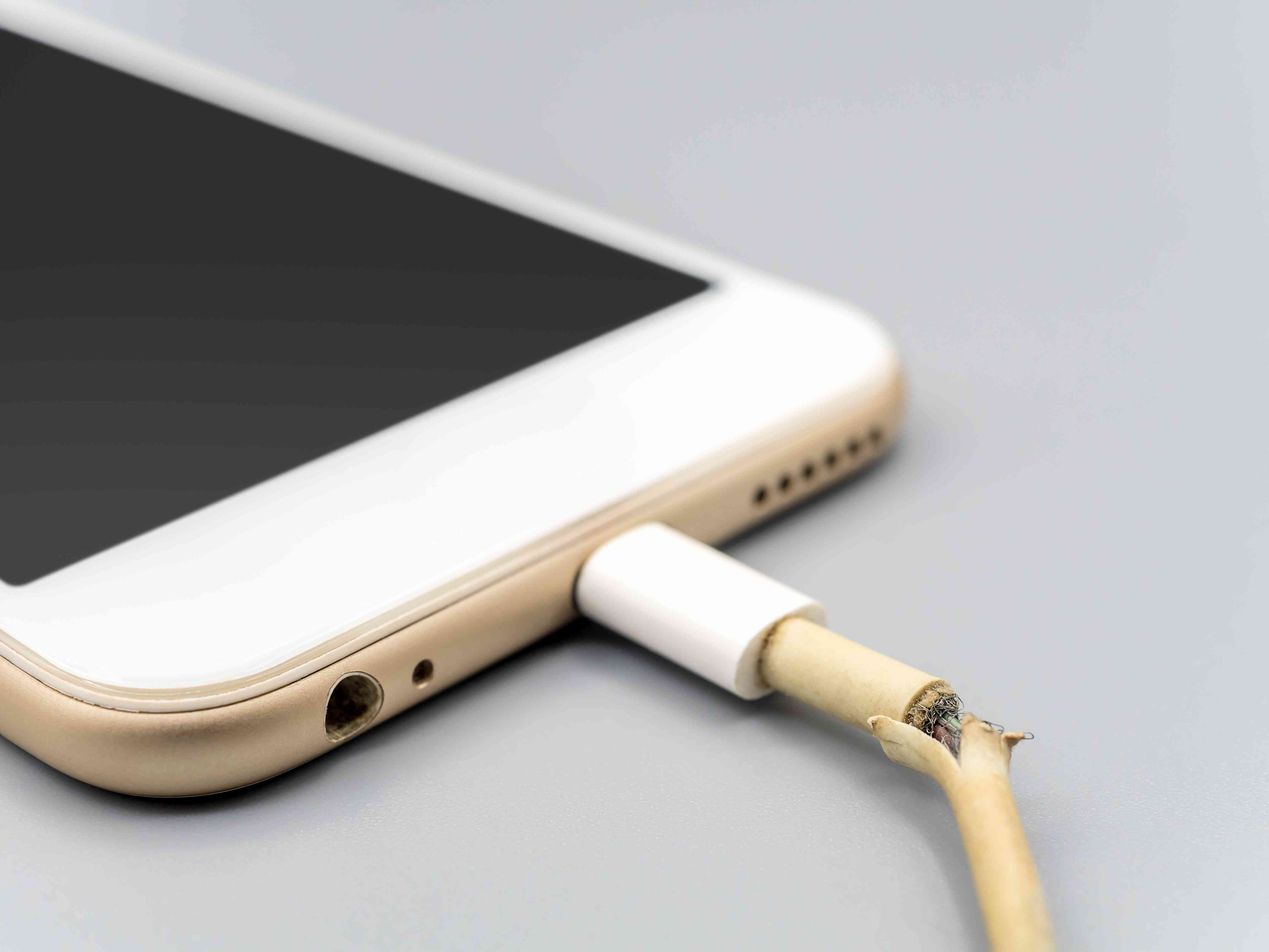 A damaged Lightning cable plugged into an iPhone.