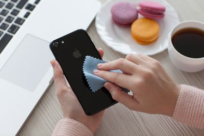 A woman cleaning an iPhone with a cloth