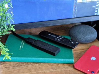 An unresponsive Fire Stick with a remote in front of a TV.