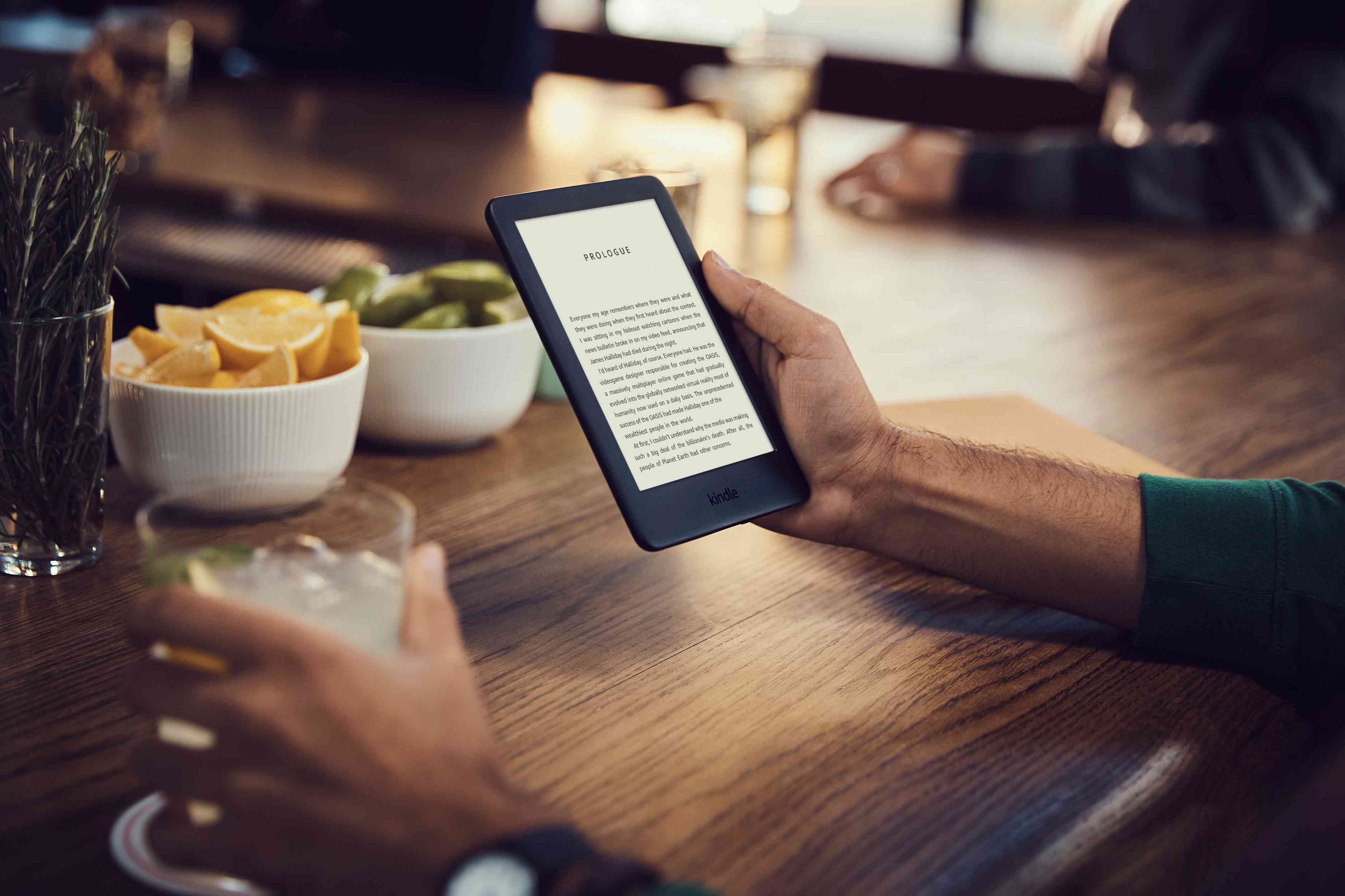 Someone reading an e-book on a Kindle device at the bar in a café.