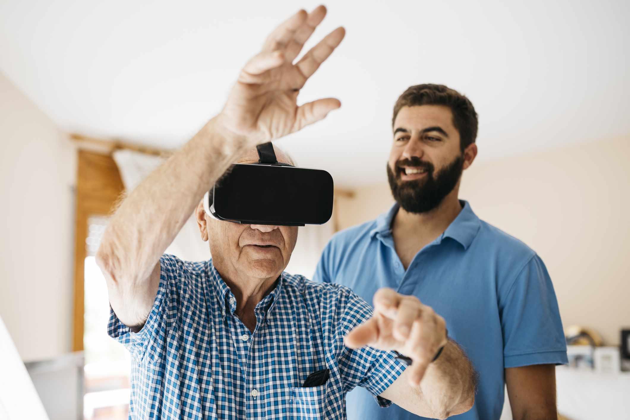 Senior man using Virtual Reality Glasses at home while his adult grandson watching him
