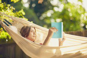 Teenage boy relaxing in garden hammock reading a book