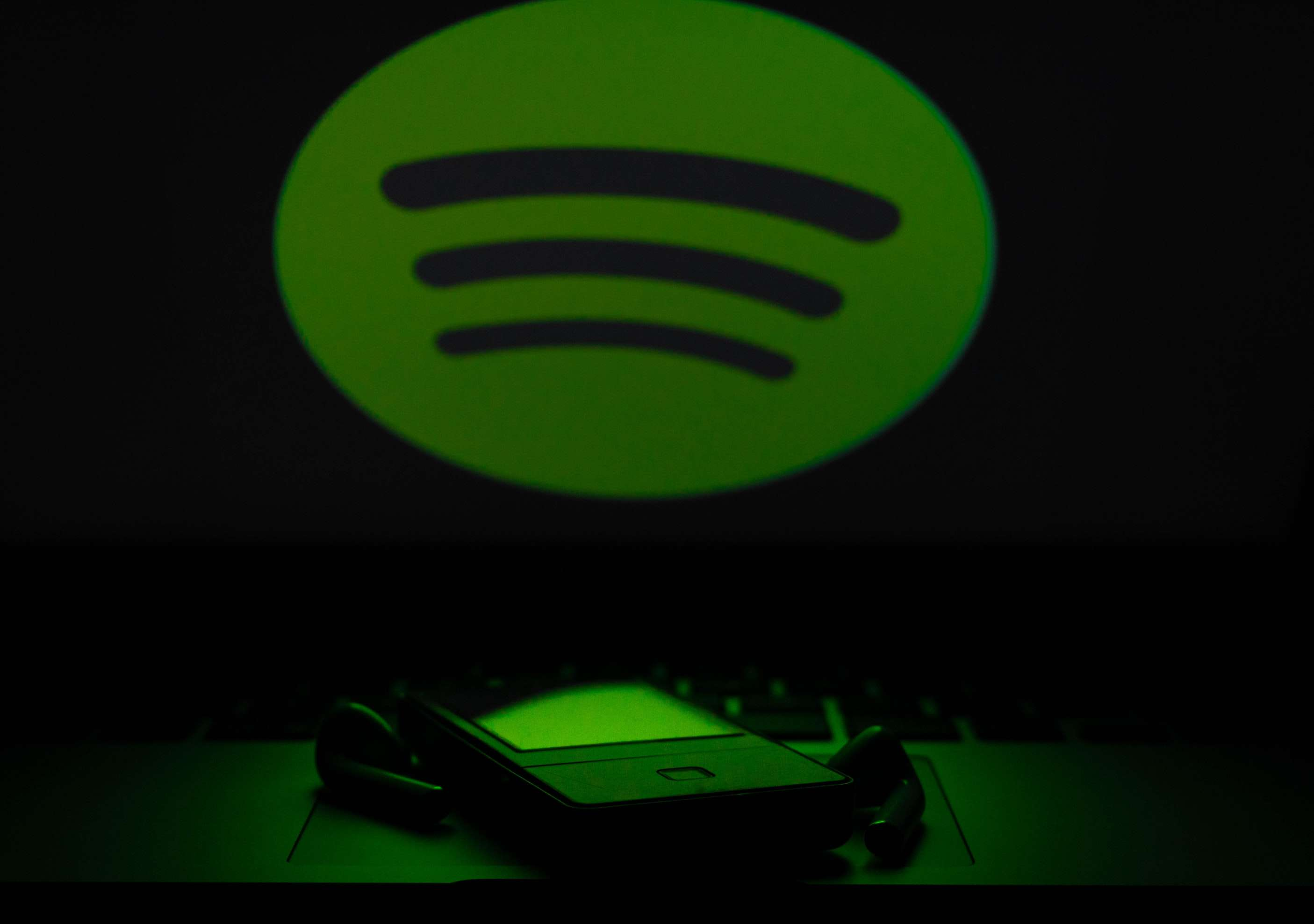 The Spotify logo looming over an mp3 player and headphones