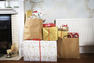 Photo of holiday gifts next to a fireplace