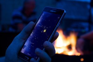 Someone using a star gazing app on their phone by a campfire.