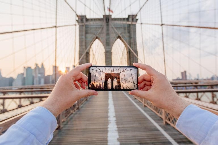 Personal perspective view of a man photographing Brooklyn Bridge for a photo for Instagram's Explore Page