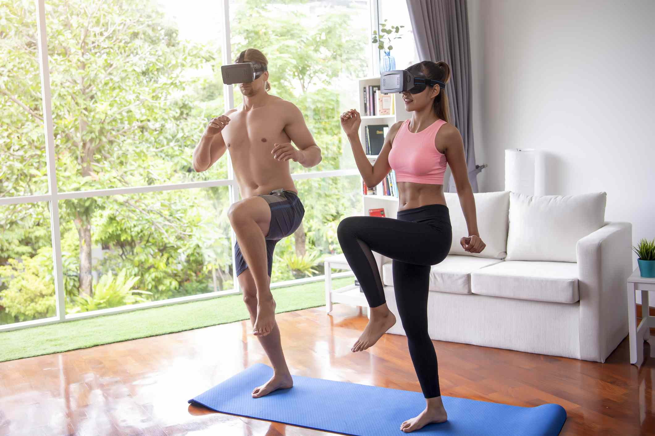 Two people exercising while wearing VR headsets in a living room.