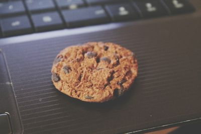 Chocolate chip cookie on a laptop keyboard representing internet cookies