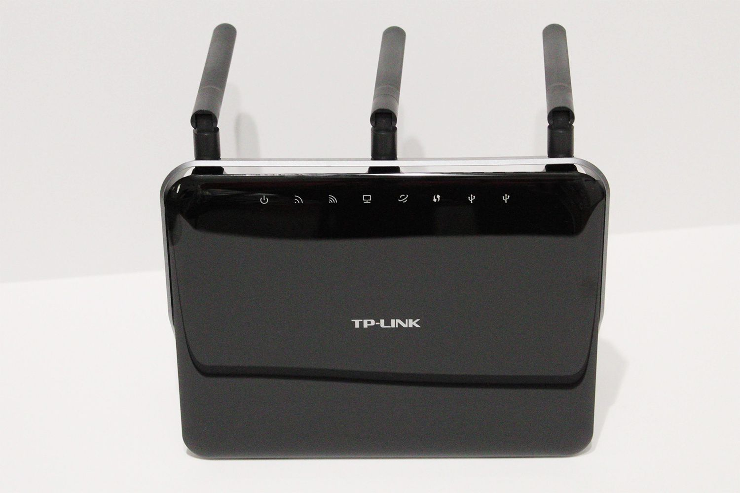 The TP-Link Archer C9 AC1900 is a budget-friendly router, so it doesn't include too many of the features you see in newer, more expensive models. It doesn't include Alexa control or MU-MIMO technology, but it's supposed to provide a long signal range for larger homes, as well as support fast enough speeds for online gaming and 4K media. I tested the TP-Link AC1900 alongside several other long range routers to see how well it performs in the real world. Design: Fingerprints galore The Archer AC1900 definitely isn't the most attractive router I've seen. The version I tested is black, but TP-Link also makes the C9 in white. The gloss finish gives the AC1900 a cheap look, and it unfortunately shows each and every smudge and fingerprint when you touch the surface. The indicator lights sit on the front face, and you can easily see the network status with a quick glance. The C9 has a slate grey plastic border, which goes around the top perimeter, angles outward, and serves as a stand for the router. The stand allows you to position the AC1900 horizontally or vertically. However, you'll have to move your cabling under the stand to place the router in a horizontal position, so you can't easily move it between the two orientations without disconnecting your cables. The Archer C9 has three removable antennas you can swivel and adjust. Although they're a necessary evil, the antennas are extremely long (almost six inches), so the router looks oddly tall when in the vertical position with the antennas extended. Most of the ports are positioned on the rear, with the exception of the second USB port that sits along the side next to the Wi-Fi button. Setup: Takes less than 10 minutes Setup is simple, and you can use the Tether app or the TP-Link site. There's a QR code in the quick setup leaflet, so you can easily find the app. As it goes with most routers, you'll find a temporary network name, password, and login info on the label. The app walks you through the setup process step-b