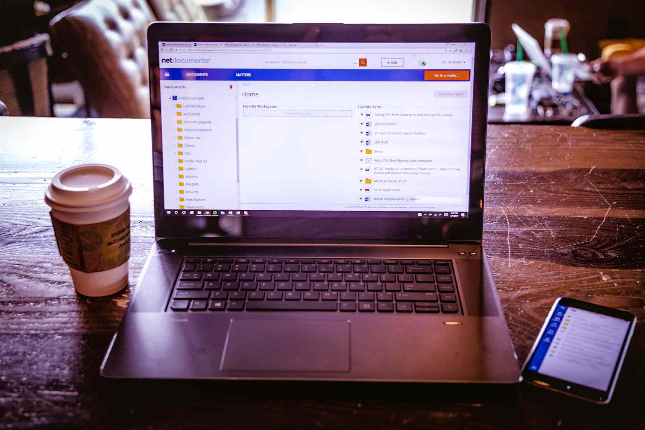 Laptop in cafe displaying folder full of PDF files