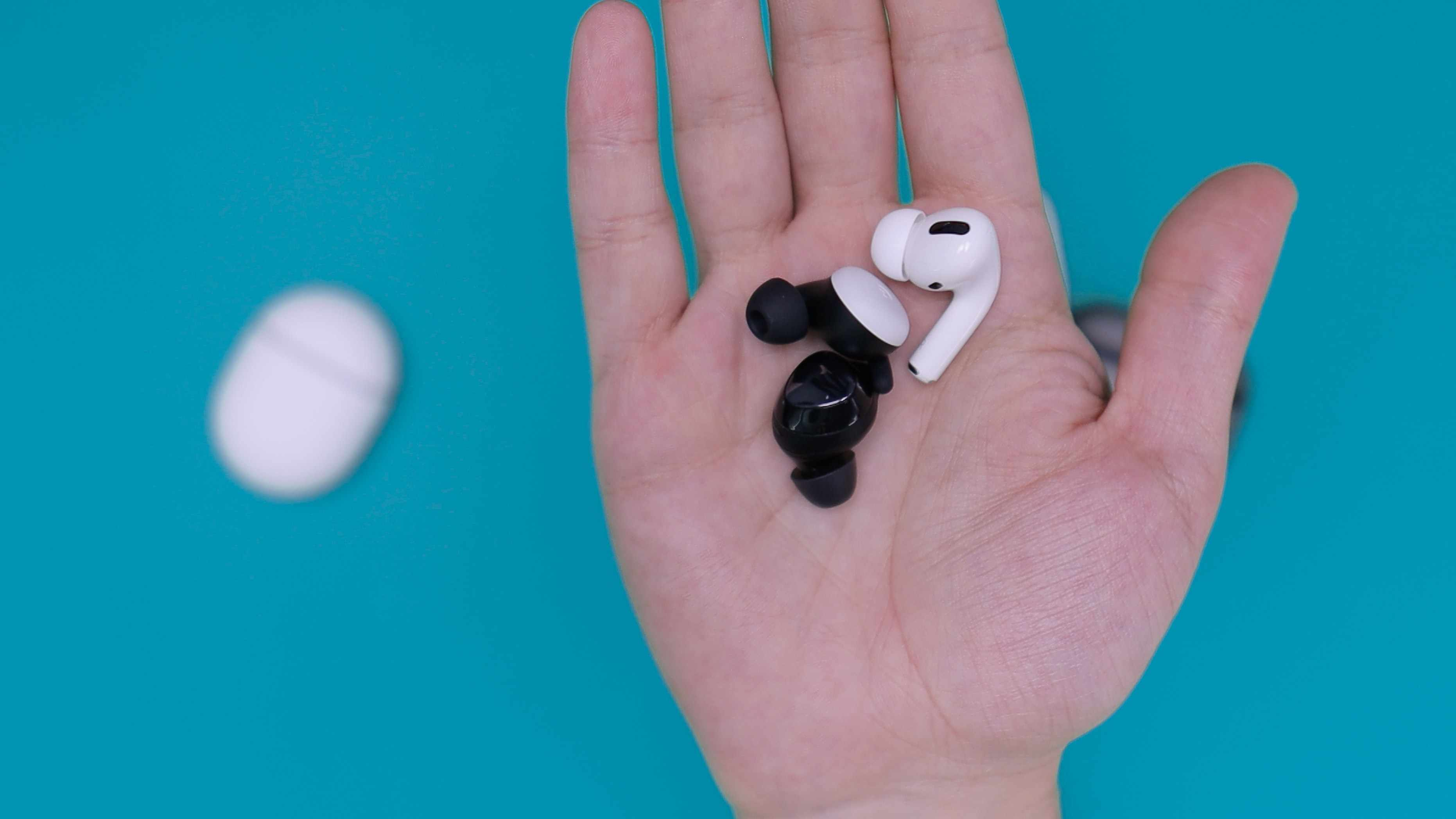 Closeup of someone holding several earbuds with a case in the background.