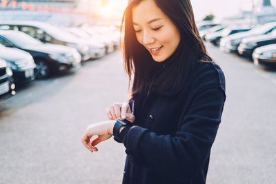 A woman smiling at her smart watch that's on her wrist