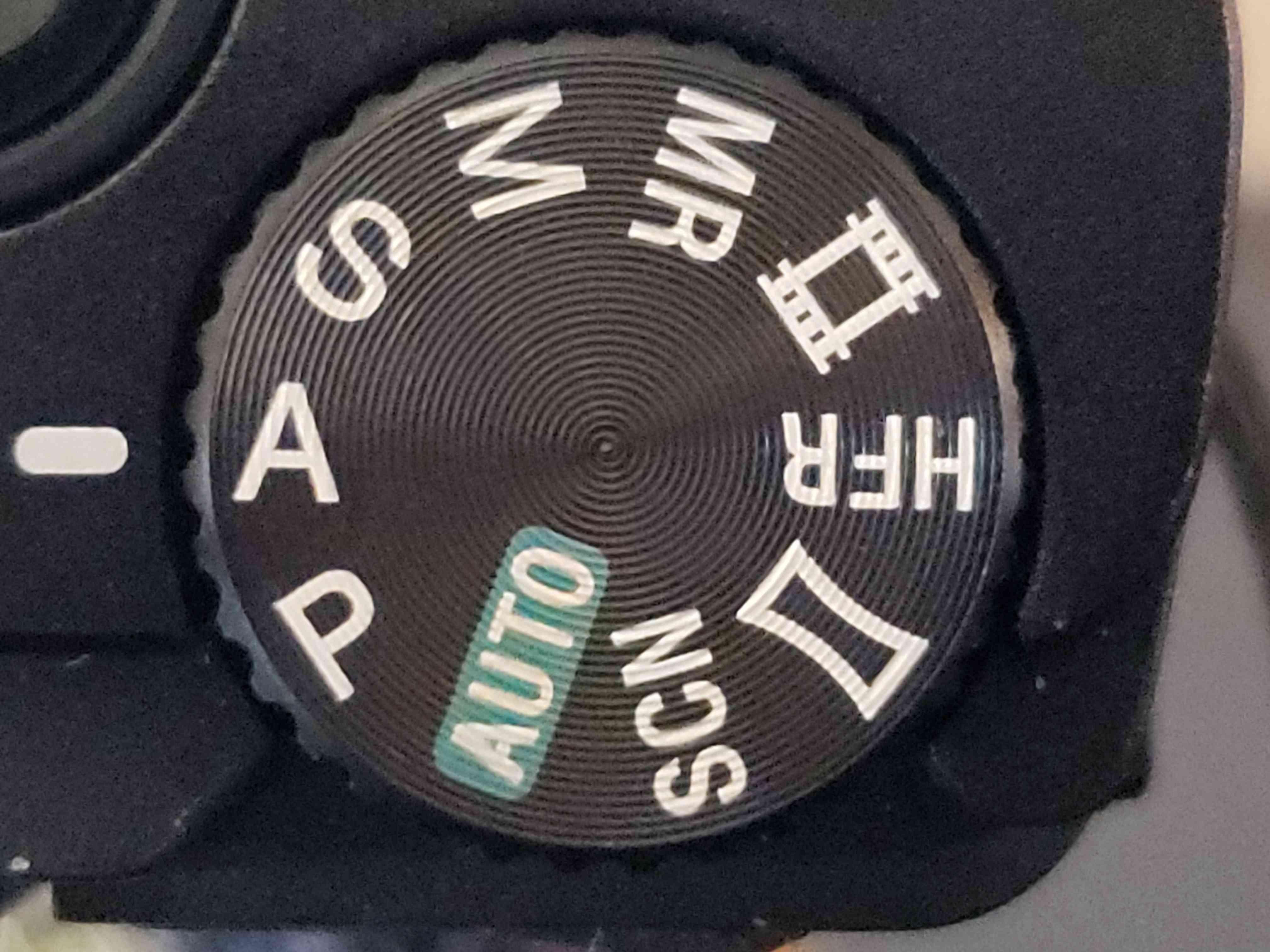 A close up of a camera mode dial.