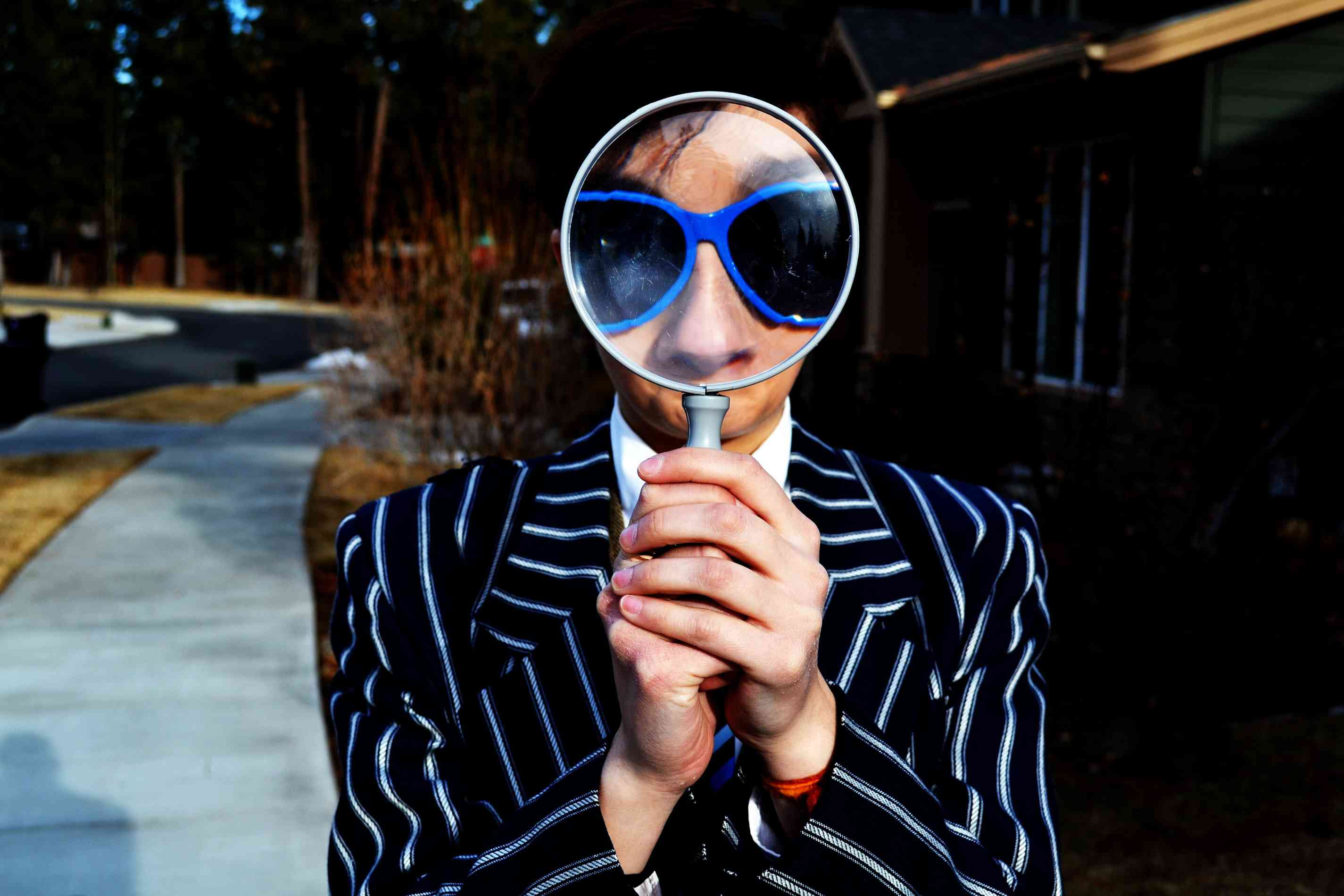 person using magnifying glass to enlarge their face