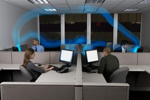 Businesspeople in cubicles,computers connected by stream of blue light
