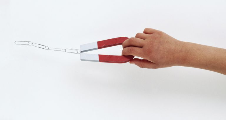 Hand holding horseshoe magnet with suspended paperclip chain