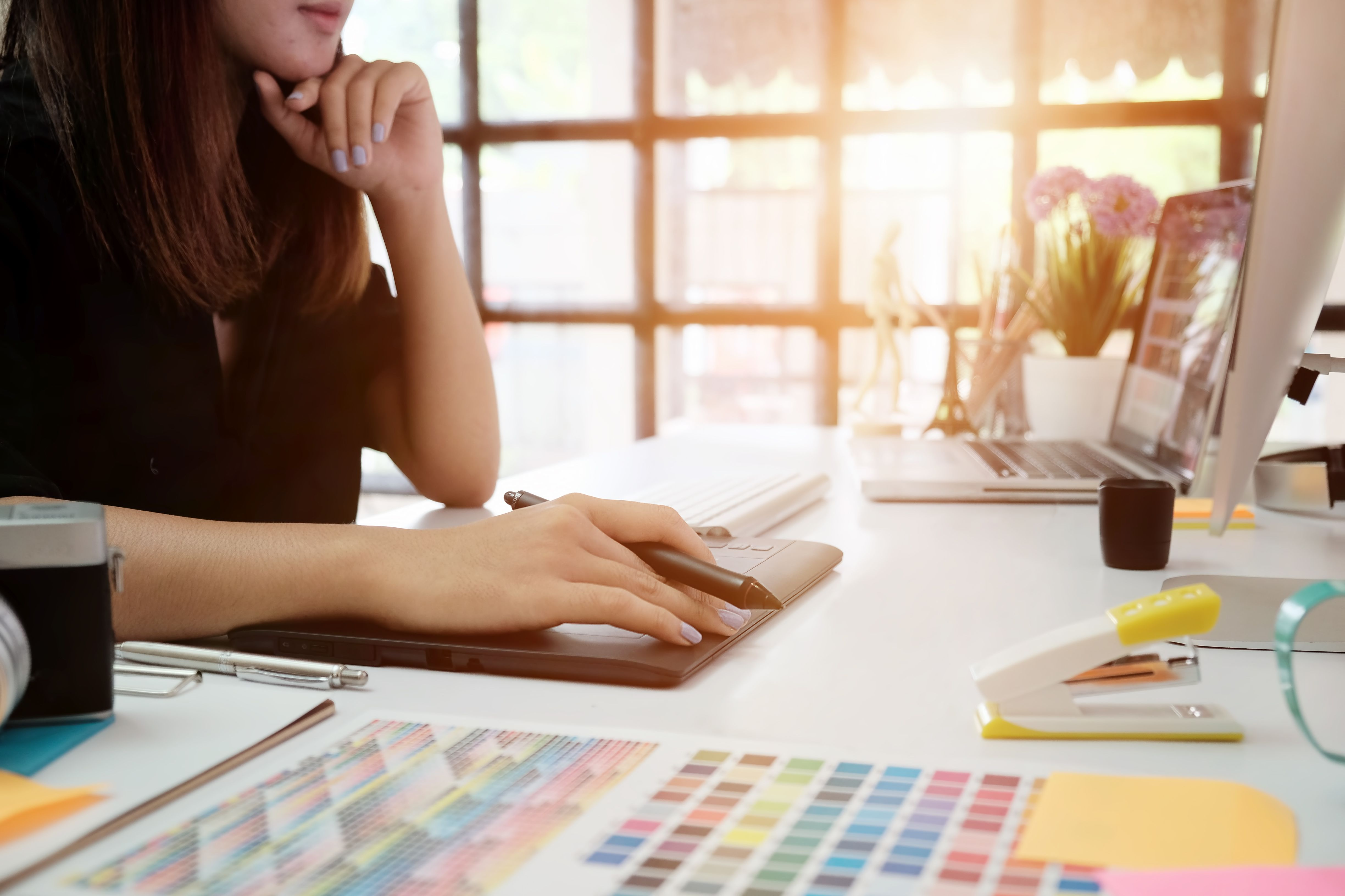 Midsection Of Woman Using Graphics Tablet At Table In Creative Office