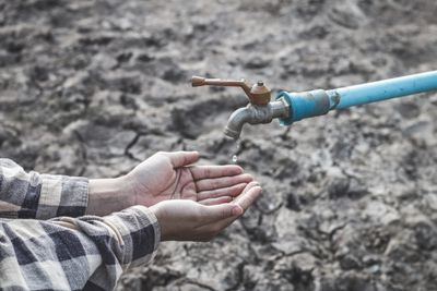Cropped image of hands cupped to catch water beneath a dripping faucet during a drought.