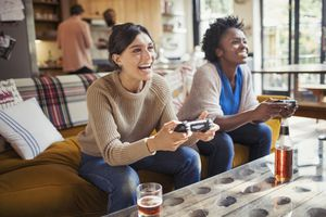 Women sitting on a couch playing video games.