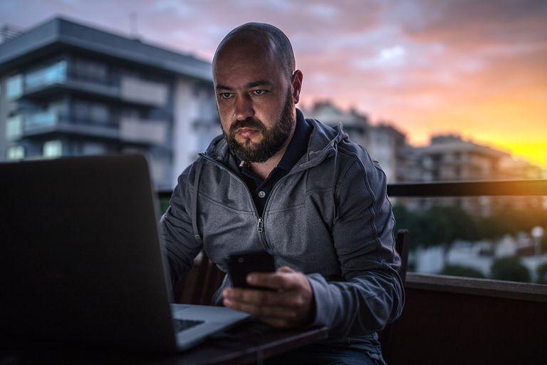 Bald and bearded man uses laptop and smartphone at sunset.