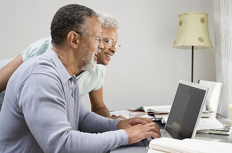 Couple in their home office looking at a laptop