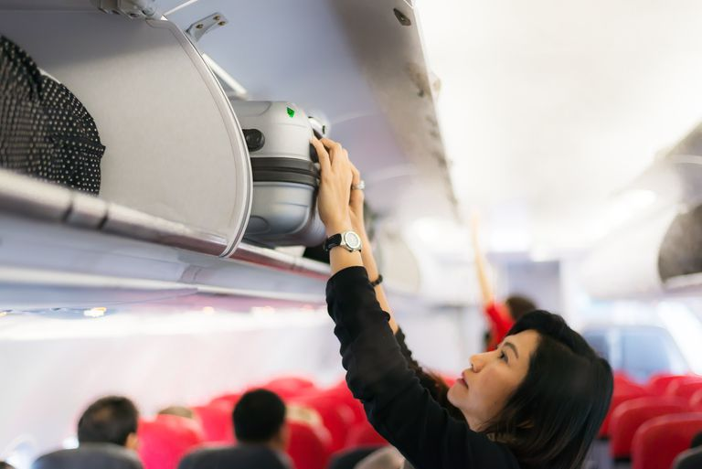 A woman putting a carry on bag in an overhead bin.