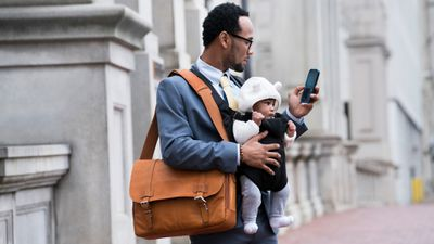 Businessman with glasses holding a bag, a baby, and an iPhone.