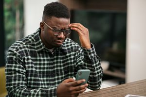 Frustrated man looking at his iPhone