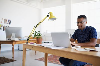 Man sitting at table with laptop and papers, hard at work