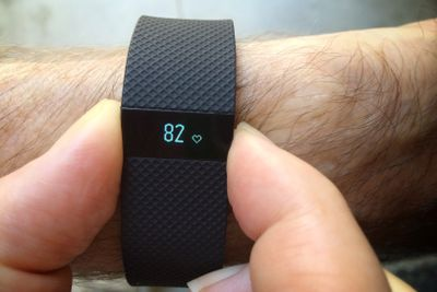 A Fitbit displaying heart rate on a wrist.
