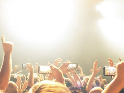 A crowd filming a concert on their smartphones