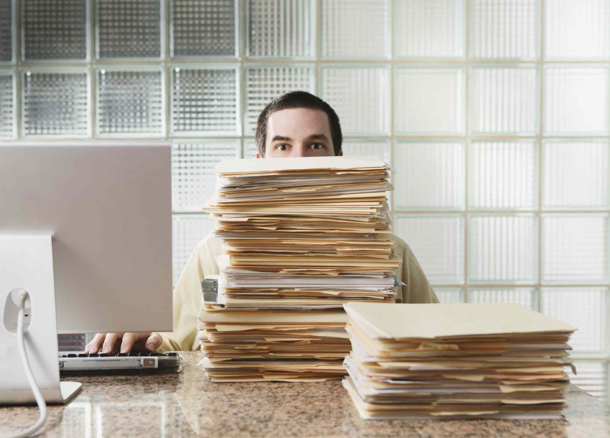 Overworked businessperson with a stack of files and a computer