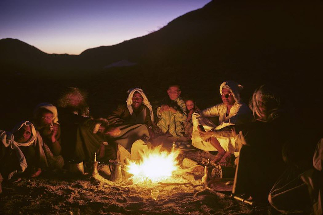 A group sitting around a campfire telling stories like those in the Knifepoint Horror podcast.