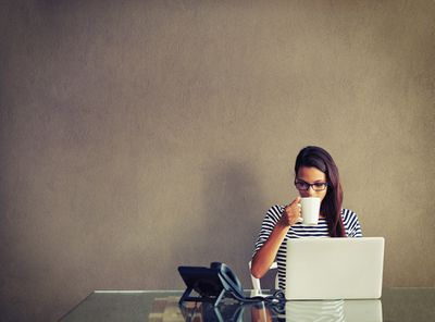 Woman drinking coffee at desk using her computer
