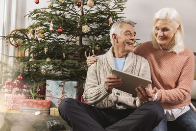 A couple looking at a tablet computer in front of Christmas tree