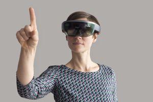 Woman wearing mixed reality smartglasses raising her hand