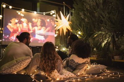 Four people watching a movie on a projection screen in a backyard