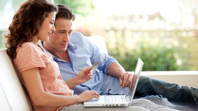 A man and woman shopping on the AliExpress website on their laptop computer