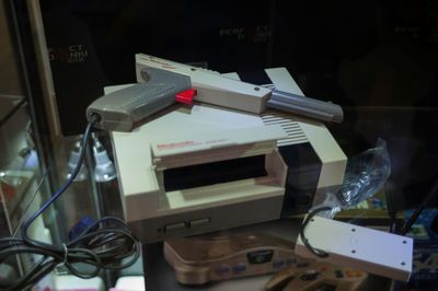 The Nintendo Entertainment System and the NES zapper gun on a glass table