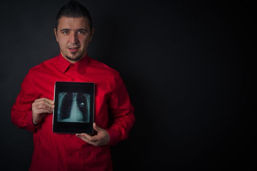 Man holding chest x-ray with pacemaker on digital tablet over his chest.