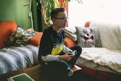 Young boy playing game console