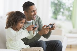 A man and his daughter hold games controllers while smiling together